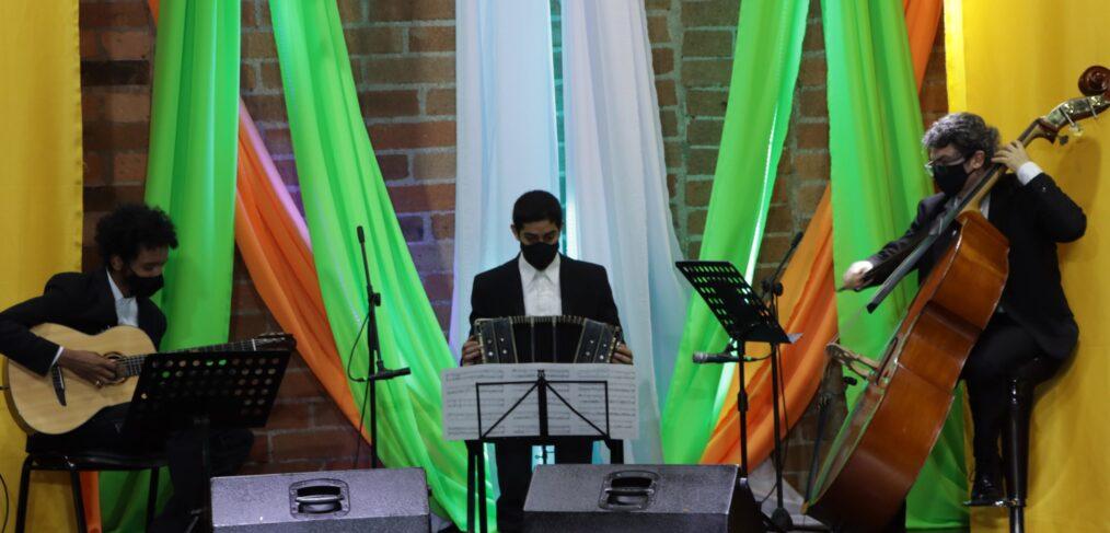 grupo musical tocando, guitarra a la izquierda, acordeón en el centro y a la derecha contrabajo