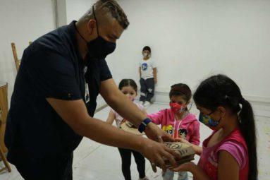 niños recibiendo materiales para manualidades