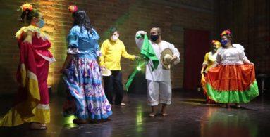 muestra de baile en escenario con verstidos coloridos