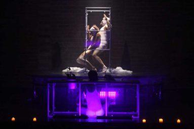 Personas sobre plataforma con luz púpura en escenario