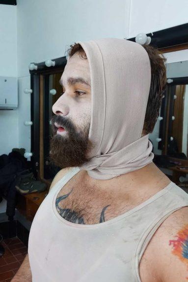 hombre con barba maquillado en blanco y con vendas