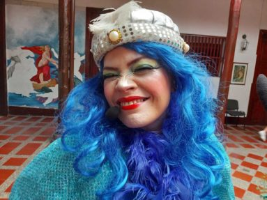 Mujer disfrazada con cabello azul, gorro blanco con brillos