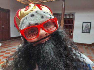 hombre con barba negra con gafas rojas y gorro en forma de corona